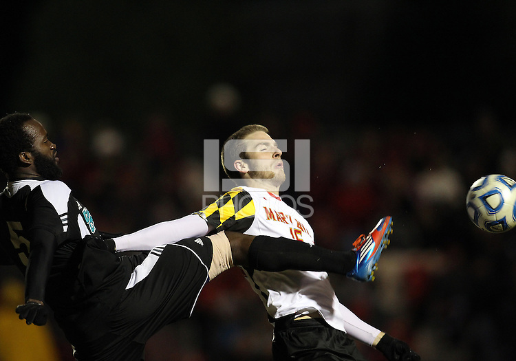 COLLEGE PARK, MD - NOVEMBER 25, 2012: Patrick Mullins (15) of the University of Maryland has the ball poked away by Jhamie Hyde (5) of Coastal Carolina University during an NCAA championship third round match at Ludwig Field, in College Park, MD, on November 25. Maryland won 5-1.