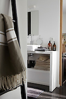 The adjacent bathroom is separated from the bedroom by a sliding door in natural wood