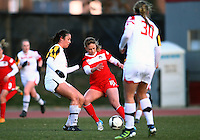 COLLEGE PARK, MARYLAND - April 03, 2013:  Caroline Miller (10) of The Washington Spirit  is tackled by Marisa Kresge (6) of the University of Maryland women's soccer team in a NWSL (National Women's Soccer League) pre season exhibition game at Ludwig Field in College Park Maryland on April 03. Maryland won 2-0.