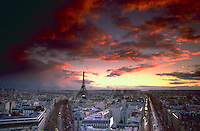 Aerial view at sunset beneath scattered clouds from the Arc de Triomphe of the Paris city skyline including the Eiffel Tower.<br />