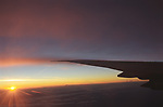 Looking  out, the view from an airplane window. Flying above the clouds, deep dusk evening light South America. 2002 2000s.