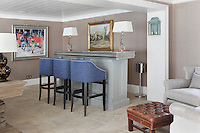 A bar with three stools stands at one end of the spacious dining room, along with a pair of armchairs and a leather foortstool for relaxing before dinner