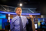 NY1 anchor Pat Kiernan puts his jacket on after taking his microphone off, on set on April 20, 2012 in New York City.  (Photo by Michael Nagle)