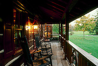 Porch of log home with rocking chairs as dusk begins, with porch light on