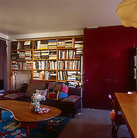 A living room with a purple sofa with built in bookshelves and a red cupboard against one wall behind. A stainless steel floor lamp stands nearby and a curved wooden coffee table is placed in front.