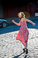 Woman running across cobblestone street, rear view