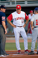 Team Canada manager Ernie Whitt #12 meets with the umpires at home plate prior to the game against Team USA at the USA Baseball National Training Center, September 4, 2009 in Cary, North Carolina.  (Photo by Brian Westerholt / Four Seam Images)