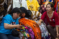 Yogyakarta, Java, Indonesia.  Young Women Checking Cell Phone in a Clothing Shop, Beringharjo Market.