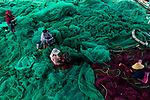 Workers sit among a sea of turquoise nets as they repair holes torn in them by fish.  The flowing nets are repaired by women who work all day to make sure they are ready before they are used at sea to catch anchovies and tuna.<br /> <br /> Banker and amateur photographer, Nguyen Sanh Quoc Huy, captured the beautiful images in Nha Trang fishing port in Vietnam.  SEE OUR COPY FOR DETAILS.<br /> <br /> Please byline: Nguyen Sanh Quoc Huy/Solent News<br /> <br /> © Nguyen Sanh Quoc Huy/Solent News & Photo Agency<br /> UK +44 (0) 2380 458800