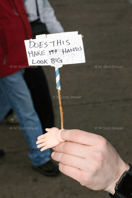 """A man holds a small rubber hand and protest sign reading """"Does this make my hands look big,"""" as People gather in the National Mall area of Washington, DC, for the Women's March on Washington protest and demonstration in opposition to newly inaugurated President Donald Trump on Jan. 21, 2017. The sign is a reference to frequent jokes about the size of Donald Trump's hands."""