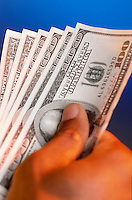 Detail of a hand holding $100 dollar bills.