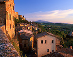 Tuscany, Italy      <br /> Evening sun on the tiled roofs and walls of homes in Montepulciano with Monte Amiata in the distance above the Val d'Orcia
