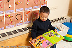 Education preschool 3-4 year olds boy sitting by himself looking at picture book horizontal