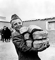 Polish youngster with his arms loaded down with bread made from flour supplied by the American Red Cross.  Smile is in anticipation of enough bread to eat, something he would not get if he had stayed in his native Poland, Russia, ca. 1943. OWI.  (Army)<br /> Exact Date Shot Unknown<br /> NARA FILE #:  111-SC-170234<br /> WAR & CONFLICT BOOK #:  1256