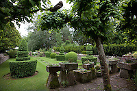 Two rows of topiary box clipped into boldly shaped tiers form an avenue leading to yet another part of the garden