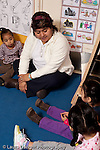 Educaton preschool 3-4 year olds circle time with female teacher talking to group vertical bil9ingual Spanish English signs on wall