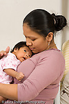 newborn baby girl one month old  Mexican American with mother held vertical