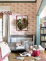 In a girl's pretty bedroom, the walls are in a Waterhouse Wall hangings white and pink floral print; the trim is in Caldwell Green; an Oeuf toddler bed is topped with a comforter in a Schumacher fabric.