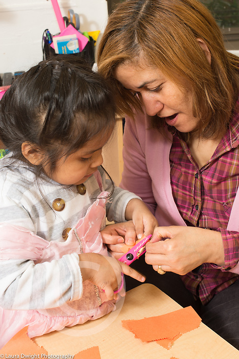 Education Preschool 3 year olds female teacher working with girl learning to use scissors