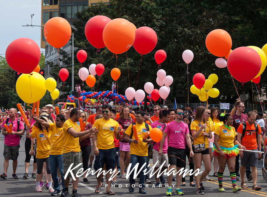 Group wearing red, orange, yellow and pink shirts holding ballons supporting gay rights, Seattle PrideFest Parsade 2015, Washington State, WA, America, USA.