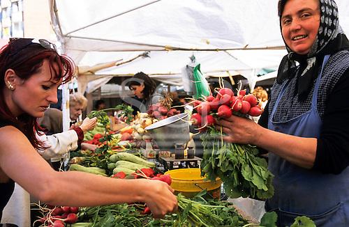 Bucharest, Romania. Smiling market seller holding a bunch of large radishes; shopper choosing.