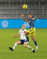 ORLANDO, FL - JANUARY 22: Catalina Usme #11 jumps to head the ball while defended by Julie Ertz #8 during a game between Colombia and USWNT at Exploria stadium on January 22, 2021 in Orlando, Florida.