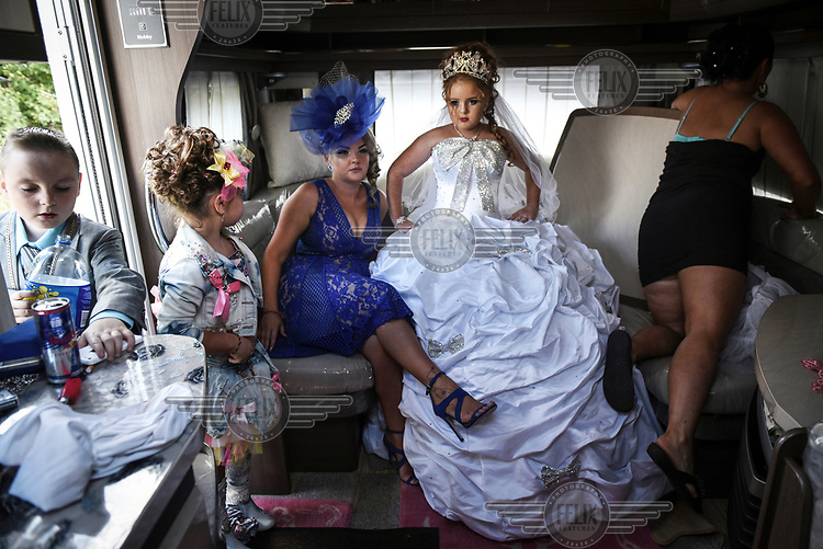 Irish Traveller Viviana and her family prepare for her First Holy Communion in her family's trailer, parked in a car park. Seated beside her is her aunt Precious whose son Michael is also celebrating his Holy Communion with his cousins.
