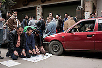 Men kneel down to pray, taking a break from protesting on a side street off Tahrir Square where the main protest is occuring. Continued anti-government protests take place in Cairo calling for President Mubarak to stand down. After dissolving the government, Mubarak still refuses to step down from power.