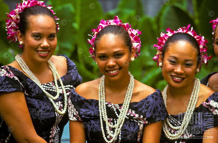 Three Polynesian dancers wearing flower leis following a hula performance, Lei Day celebration at Hilton Hawaiian Village Hotel