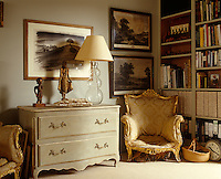 A modern chest of drawers is flanked by a pair of restored Georgian armchairs in this cosy London drawing room