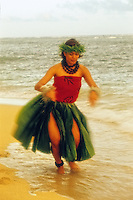 Hula dancer on the beach wearing ti leaf skirt