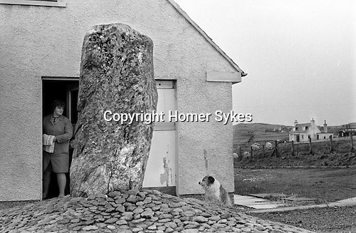 Callanish Standing Stones. Outlying stone in the Stonefields council housing estate, 1974. Callanish Isle of Lewis and Harris, Scotland UK. 1970s.<br /> This is house is number 14 Stonefield. The stone is Callanish XII, part of the huge network that covers that area and probably aligned with the moon in some way.