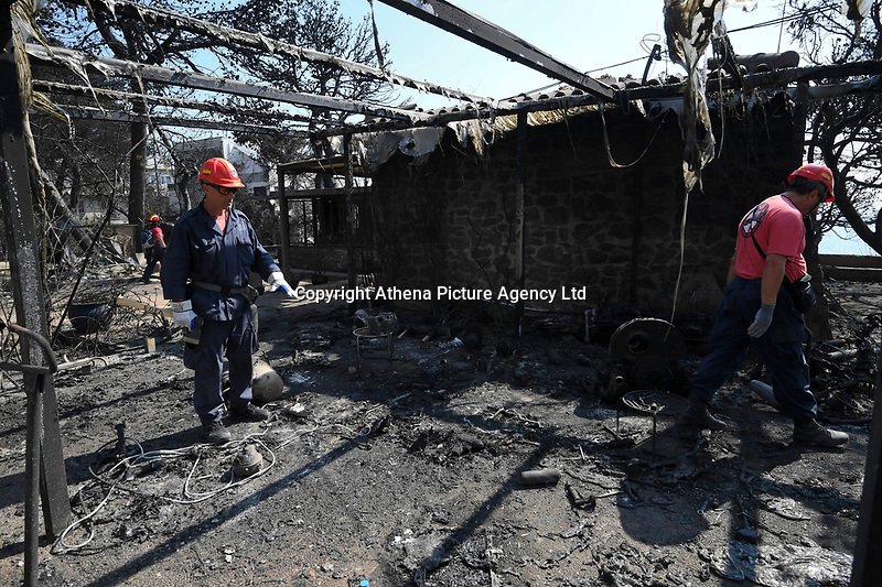 Pictured: Fire fighters assess the damage in the aftermath of the forest fire which has claimed dozens of lives in the Mati area of Rafina, Greece. Wednesday 25 July 2018<br /> Re: Deaths caused by wild forest fires throughout Greece.