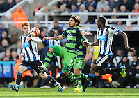 Alberto Paloschi of Swansea City (centre) is closed down by Jack Colback (left) of Newcastle United and Chancel Mbemba of Newcastle United during the Barclays Premier League match between Newcastle United and Swansea City played at St. James' Park, Newcastle upon Tyne, on the 16th April 2016