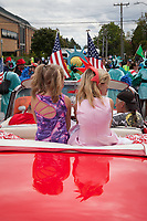 Two girls sitting on back of red Cadillac, Independence Day Parade 2016, Burien, Washington, USA.