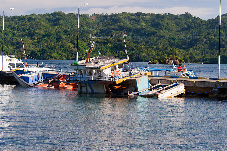 A fishing boat has sunk inside the jetty at the marine police station dock, where The Lembeh Resort picks up and drops off guests on North Sulawesi, Indonesia.  (Lembeh Island is prominent in the background, on the other side of the strait.)