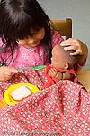 Preschool girl feeding doll pretend play vertical