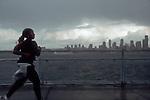 Seattle, African American woman jogger running in rain, skyline, Alki Point, West Seattle, Elliott Bay, Puget Sound, Washington State, Pacific Northwest, USA.