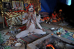 A Naga Sadhu (naked saint) in a yoga posture at Juna Akhara tent at Kumbh mela on 13th February 2010. Haridwar, Uttara Khand, India, Arindam Mukherjee