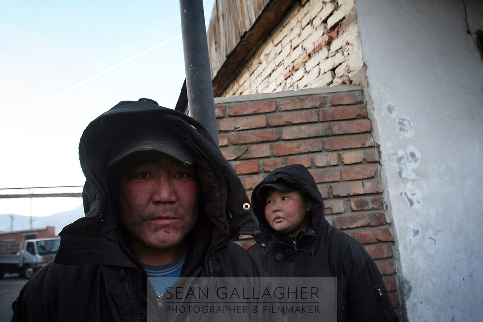 MONGOLIA. Ulaan Baatar. Otguntugs (left) the father and Ounsuren (right) the mother, wait for a local market to open so that they can buy vodka early in the morning. As the global financial crisis grips Asia, Mongolia is feeling the implications first hand as the country suffers from rising inflation pushing the price of food and fuel ever upwards. For the country's homeless, who live in sewers and abandoned garages in the capital and already face extreme discrimination and are denied access to basic health and social care, their lives are hanging in the balance. 2008