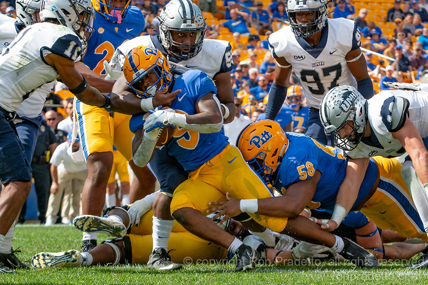 Pitt running back Rodney Hammond scores on a two-yard touchdown run despite the efforts of New Hampshire defensive lineman Duval Paul (55). The Pitt Panthers defeated the New Hampshire Wildcats 77-7 at Heinz Field, Pittsburgh, Pennsylvania on September 25, 2021.