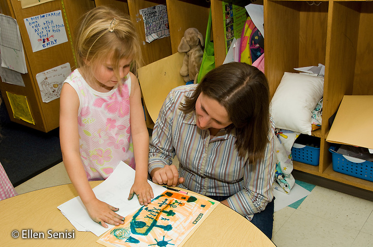 """MR / College Park, Maryland.Center for Young Children, laboratory school within the College of Education at the University of Maryland. Full day developmental program of early childhood education for children of faculty, staff, and students at the university..Student (girl, 5) explains her drawing / story to teacher. It has """"yes"""" and """"no"""" buttons..MR: Her7 Say1 .© Ellen B. Senisi"""