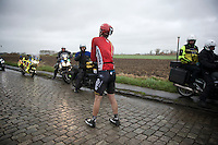 Stig Broeckx (BEL/Lotto-Soudal) waits for the teamcar to arrive after having crashed with several other riders on the slippery cobbles.<br /> <br /> 77th Gent-Wevelgem 2015