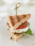 Small sandwich triangle with grilled whole wheat bread, fresh mozzarella, tomato, pesto, fresh basil