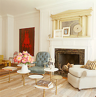 In the living room a modular brass coffee table stands between two antique armchairs in front of a marble fireplace with a neo-classical overmantel carved in stone