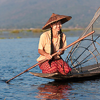 Myanmar, Burma.  Young Burmese Woman with her Canoe and Fishnet.  Inle Lake, Shan State.  She is wearing thanaka paste on her cheeks, a Burmese cosmetic sunscreen.