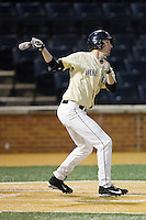Evan Stephens (5) of the Wake Forest Demon Deacons follows through on his swing against the Cincinnati Bearcats at Wake Forest Baseball Park on February 21, 2014 in Winston-Salem, North Carolina.  The Bearcats defeated the Demon Deacons 5-0.  (Brian Westerholt/Four Seam Images)
