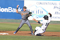 Bryant Flete #28 of the Boise Hawks throws to first base over a sliding Sheehan Planas-Arteaga #33 of the Everett AquaSox during a game  at Everett Memorial Stadium on July 25, 2014 in Everett, Washington. Everett defeated Boise, 3-1. (Larry Goren/Four Seam Images)