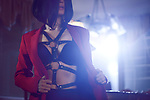 Artistic sensual portrait of a sexy young woman with short black hair taking off her red suit jacket revealing black bondage leather harness over her underwear in bright night light Image © MaximImages, License at https://www.maximimages.com