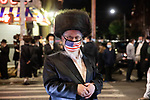 A man wears a U.S. flat face mask as he passes people protesting against COVID-19 restrictions in the Orthodox Jewish neighborhood Borough Park on Wednesday, October 7, 2020 in the Park in the Brooklyn borough of New York City.  Residents are protesting against new restrictions that would close schools, limit attendance at religious services and close non-essential businesses in areas with surges in COVID-19 cases.  Photograph by Michael Nagle